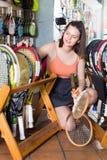 Muchacha que se coloca en camiseta en tienda de las mercancías que se divierte con la estafa Foto de archivo libre de regalías