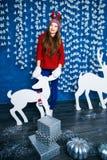 Muchacha que se coloca en decoraciones de la Navidad azul y blanca Fotografía de archivo libre de regalías