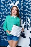 Muchacha que se coloca en decoraciones de la Navidad azul y blanca Imagen de archivo libre de regalías