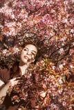 Muchacha que se coloca en el árbol Imagenes de archivo