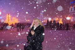 Muchacha que se coloca en el cuadrado debajo de nevadas fuertes Foto de archivo