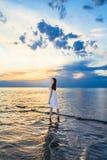 Muchacha que se coloca en el mar en la puesta del sol Foto de archivo