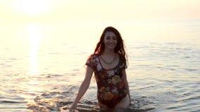 Muchacha que se coloca en el mar y la sonrisa almacen de metraje de vídeo
