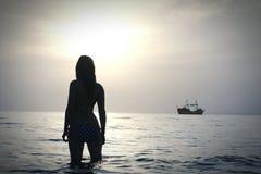 Muchacha que se coloca en el océano Imagen de archivo