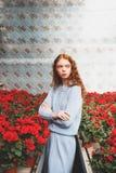 Muchacha que se coloca en flor rojo Imágenes de archivo libres de regalías