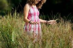 Muchacha que se coloca en hierba alta en el parque Imagen de archivo