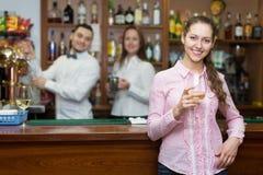 Muchacha que se coloca en la barra con el vidrio de vino Imagenes de archivo
