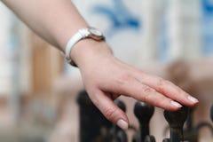 Muchacha que se coloca en la cerca y los tactos del hierro su mano imagenes de archivo