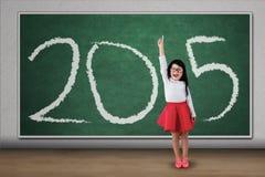 Muchacha que se coloca en la clase que forma el número 2015 Foto de archivo libre de regalías
