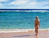 Muchacha que se coloca en la playa Foto de archivo