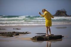 Muchacha que se coloca en la playa Foto de archivo libre de regalías