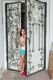 Muchacha que se coloca en la puerta Imagenes de archivo