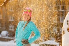 Muchacha que se coloca en nieve que cae Fotografía de archivo