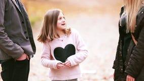 Muchacha que se coloca en parque y que habla con los padres almacen de video
