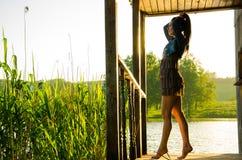 muchacha que se coloca en un embarcadero de madera Foto de archivo