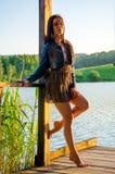 muchacha que se coloca en un embarcadero de madera Fotografía de archivo