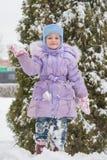 Muchacha que se coloca en una nieve del snowbank con la bola de nieve a disposición Imagenes de archivo