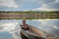 Muchacha que se coloca en una pesca del barco Imágenes de archivo libres de regalías