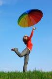 Muchacha que se coloca en una pierna con los paraguas coloridos Foto de archivo