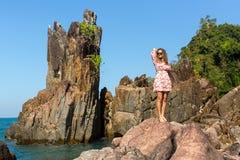Muchacha que se coloca entre las rocas en la costa de mar Imágenes de archivo libres de regalías