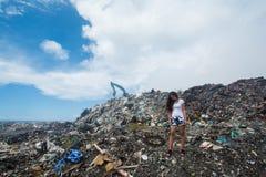 Muchacha que se coloca y que mira tristemente abajo entre basura la descarga de basura Imagen de archivo
