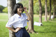 Muchacha que se coloca y que sonríe cerca de un árbol Foto de archivo libre de regalías