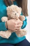 Muchacha que se considera teddybear, primer en blanco Imagen de archivo