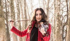 Muchacha que se considera violine en manos Imagenes de archivo