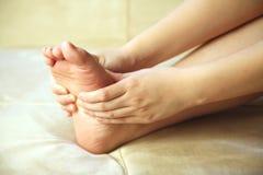 Muchacha que se da un masaje del pie Fotografía de archivo