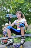 Muchacha que se detiene brevemente para una bebida mientras que patinaje sobre ruedas Fotos de archivo libres de regalías