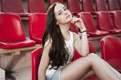 Muchacha que se divierte al aire libre Muchacha bonita que se sienta en el estadio de la escuela Fotografía de archivo