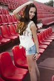 Muchacha que se divierte al aire libre Muchacha bonita que se sienta en el estadio de la escuela Imagenes de archivo