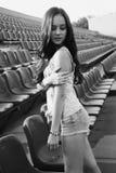 Muchacha que se divierte al aire libre Muchacha bonita que se sienta en el estadio de la escuela Foto de archivo libre de regalías
