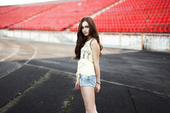 Muchacha que se divierte al aire libre Muchacha bonita que se sienta en el estadio de la escuela Fotos de archivo
