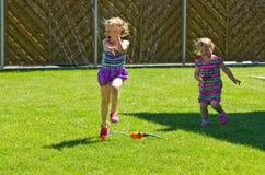 Muchacha que se divierte con la regadera en jardín foto de archivo