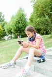 Muchacha que se divierte con su teléfono en el parque Foto de archivo libre de regalías
