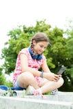 Muchacha que se divierte con su teléfono en el parque Imagenes de archivo