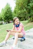 Muchacha que se divierte con su teléfono en el parque Imágenes de archivo libres de regalías