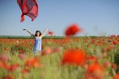 Muchacha que se divierte en amapolas con el paño del rojo del vuelo Foto de archivo libre de regalías