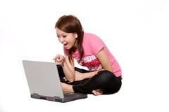 Muchacha que se divierte en línea usando la computadora portátil Foto de archivo libre de regalías