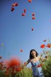 Muchacha que se divierte en un campo con las amapolas Imagen de archivo