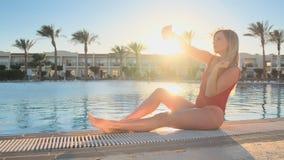 Muchacha que se divierte que toma las fotos con el teléfono móvil cerca de piscina Mujer atractiva en el traje de baño de moda ro almacen de video