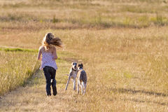 Muchacha que se ejecuta con los perros Fotos de archivo libres de regalías