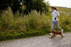 Muchacha que se ejecuta con su perro Fotos de archivo