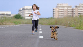 Muchacha que se ejecuta con su perro Imagen de archivo