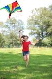 Muchacha que se ejecuta con una sonrisa al aire libre de la cometa colorida Fotografía de archivo libre de regalías