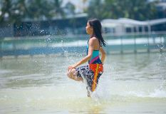 Muchacha que se ejecuta a través de la piscina que vadea en el parque del agua Imagenes de archivo