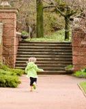 Muchacha que se ejecuta a través de un jardín Foto de archivo