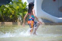 Muchacha que se ejecuta a través de una piscina que vadea en el parque del agua Fotografía de archivo libre de regalías