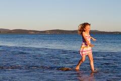 Muchacha que se ejecuta a través del mar en la puesta del sol Fotos de archivo libres de regalías